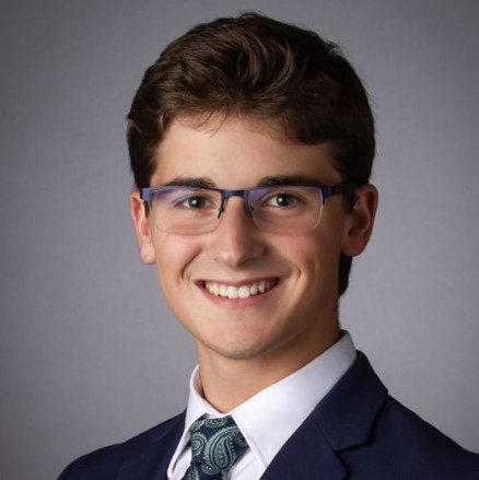 Professional photo of Brady Hanshaw wearing a navy suit and black glasses.