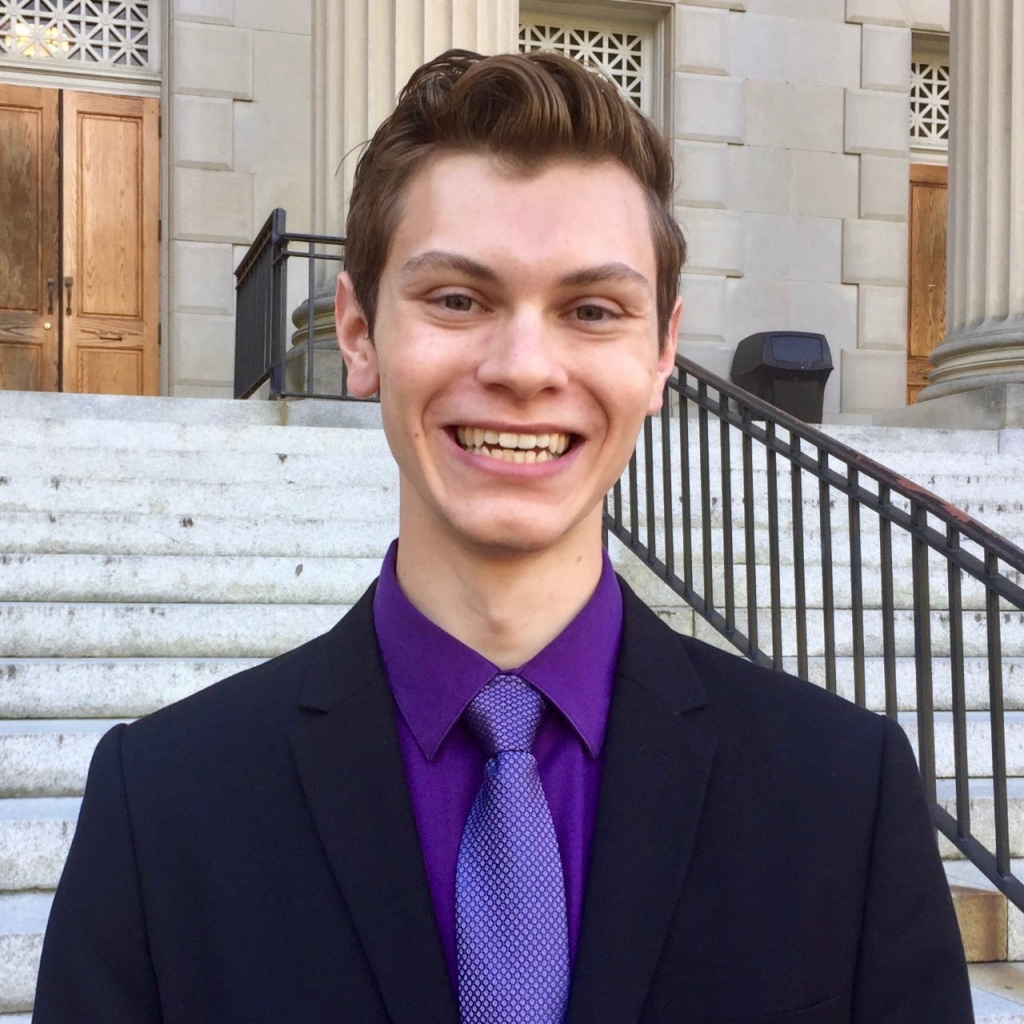 Danny Bowen smiling wearing a black suit with purple shirt and tie