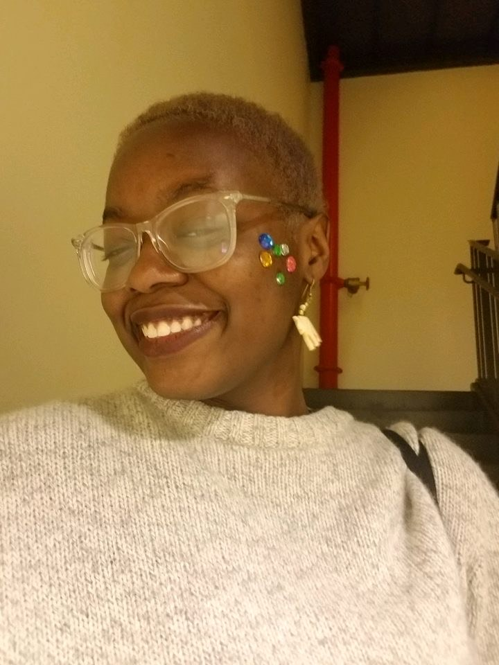 Ndobe Foletia wearing a white sweater, glasses, and stickers on their face